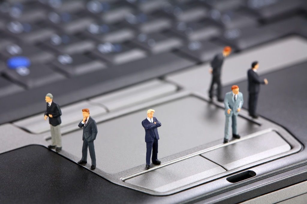 miniature-business-people-on-laptop